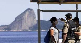 Os agentes verificam a temperatura de uma mulher usando uma máscara protetora depois que ela desce de um ônibus público, com o Pão de Açúcar em backgorund