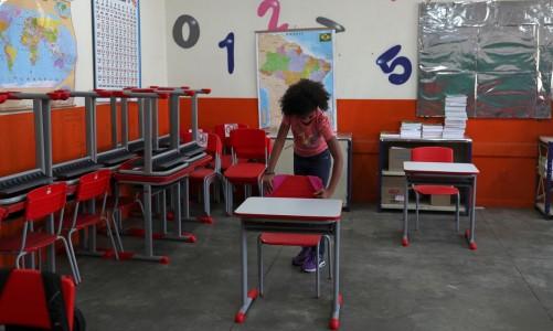 Criança pendura mochila na cadeira de sala de aula da escola Thomaz Rodrigues Alckmin, no primeiro dia de retorno das escolas do estado de São Paulo para atividades extracurriculares em meio ao surto de coronavírus (COVID-19) em São Paulo, Brasil 7 de outubro , 2020. REUTERS / Amanda Perobelli