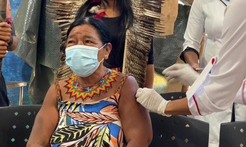 Senhora ndigéna recebendo a dose da vacina contra a covid-19
