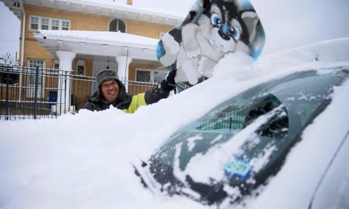 Francisco Sanchez limpa a neve de seu carro antes de sair brincar na neve com seus filhos, em El Paso. kids in El Paso