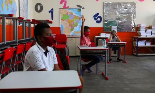Criança levanta a mão ao lado de outros alunos em sala de aula da escola Thomaz Rodrigues Alckmin, no primeiro dia de retorno das escolas do estado de São Paulo para atividades extracurriculares em meio ao surto de coronavírus (COVID-19) em São Paulo, Brasil Outubro 7, 2020. REUTERS / Amanda Perobelli