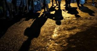 As pessoas esperam na fila para receber peixes doados por um vendedor de peixes depois de terminar seu dia de vendas no centro de abastecimento do Rio de Janeiro (CEASA) durante o surto de doença por coronavírus (COVID-19), no Rio de Janeiro