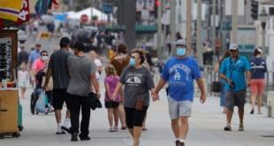 Pessoas que usam máscaras caminham ao longo do cais do oceano enquanto os Estados Unidos passaram na quinta-feira um total de mais de 4 milhões de infecções por coronavírus durante o surto global da doença por coronavírus (COVID-19) em Huntington Beach, Califórnia, EUA, em 23 de julho de 2020 REUTERS / Mike Blake