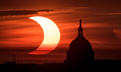 """A partial solar eclipse is seen as the sun rises to the left of the United States Capitol building, Thursday, June 10, 2021, as seen from Arlington, Virginia. The annular or """"ring of fire"""" solar eclipse is only visible to some people in Greenland, Northern Russia, and Canada. Photo Credit: (NASA/Bill Ingalls)"""