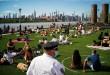 Um oficial do Departamento de Polícia de Nova York fica de olho nas pessoas que controlam a distância social em um dia quente durante o surto da doença por coronavírus (COVID-19) no Domino Park, no Brooklyn